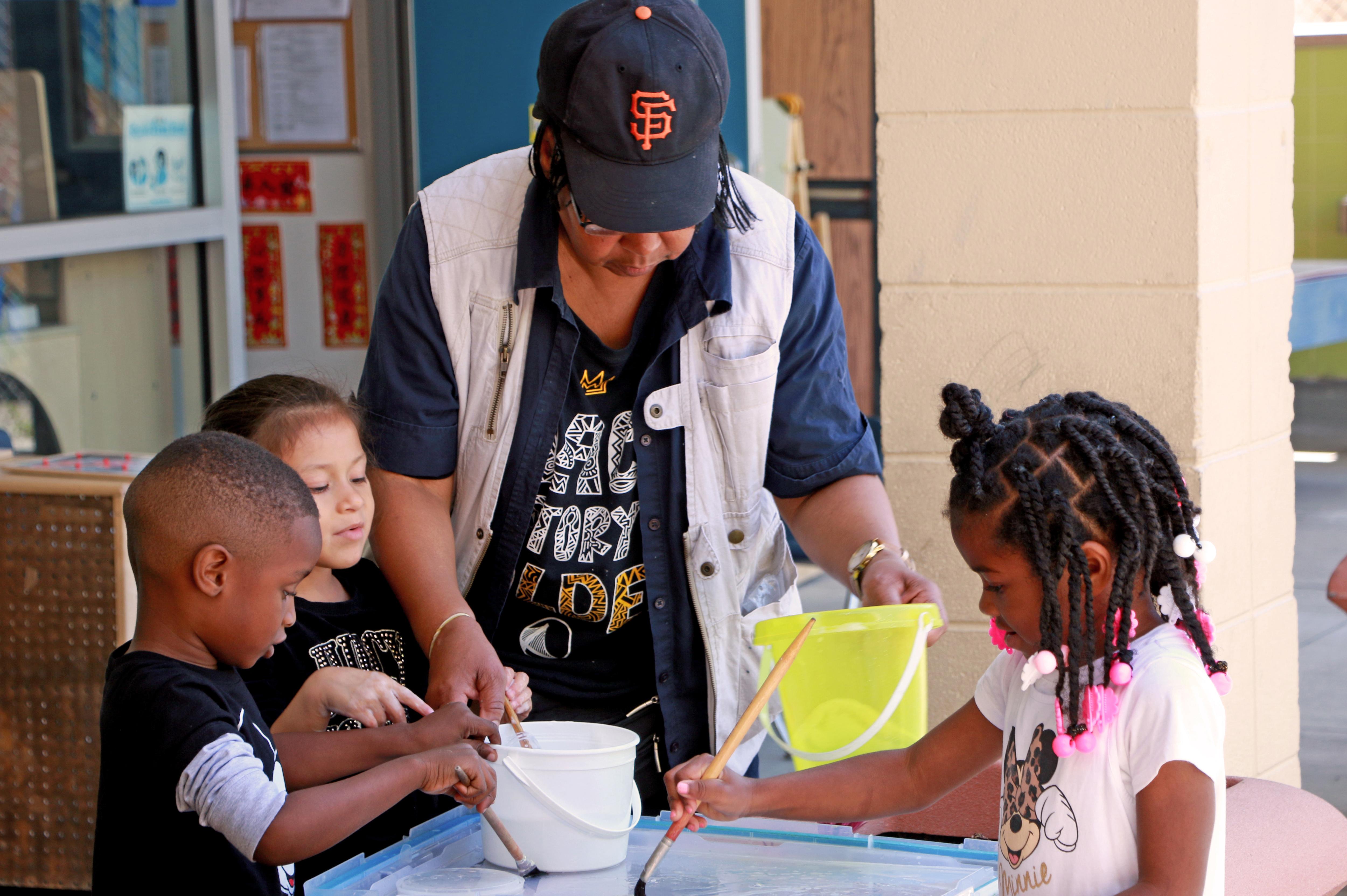 Woman helping three children paint
