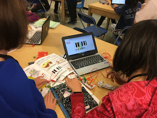 2 students look at a chromebook while touching tin foil and a fork. The foil and fork are attached to wires that are attached to the computer. They are using what is called a Makey Makey to learn what conducts electricity