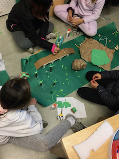 Students work to build a small model miniature golf course. They are making trees out of paper and gluing them to a big piece of green paper.