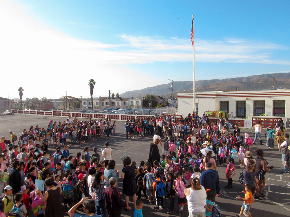 VVES Morning Circle - The whole school of students are standing in a circle, in front of the flag on the yard.