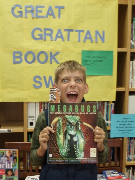 Boy making a wild face and holding a book titled Megabugs at a school literacy event