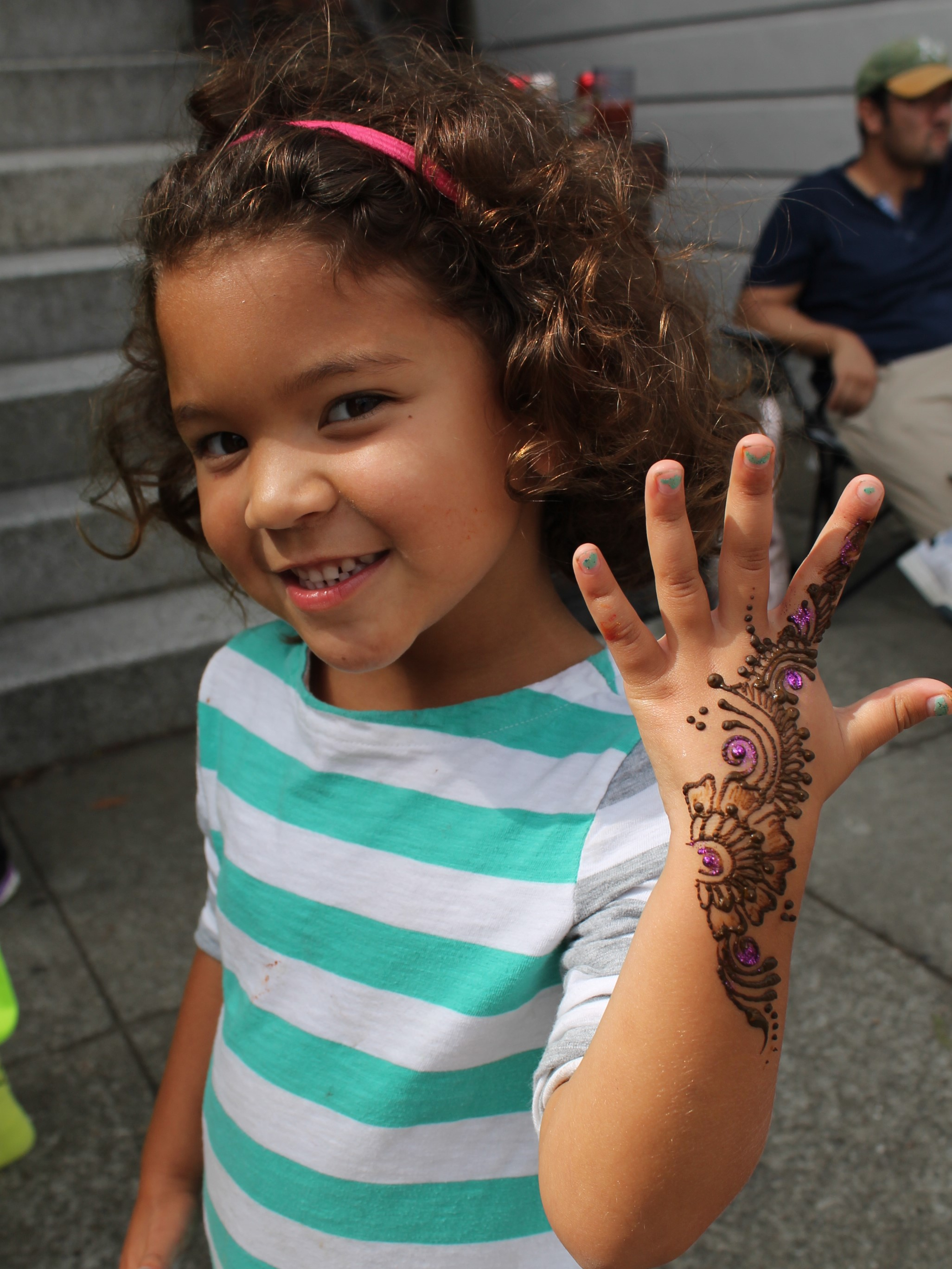 Girl showing off the henna pattern on her hand at an outdoor neighborhood festival
