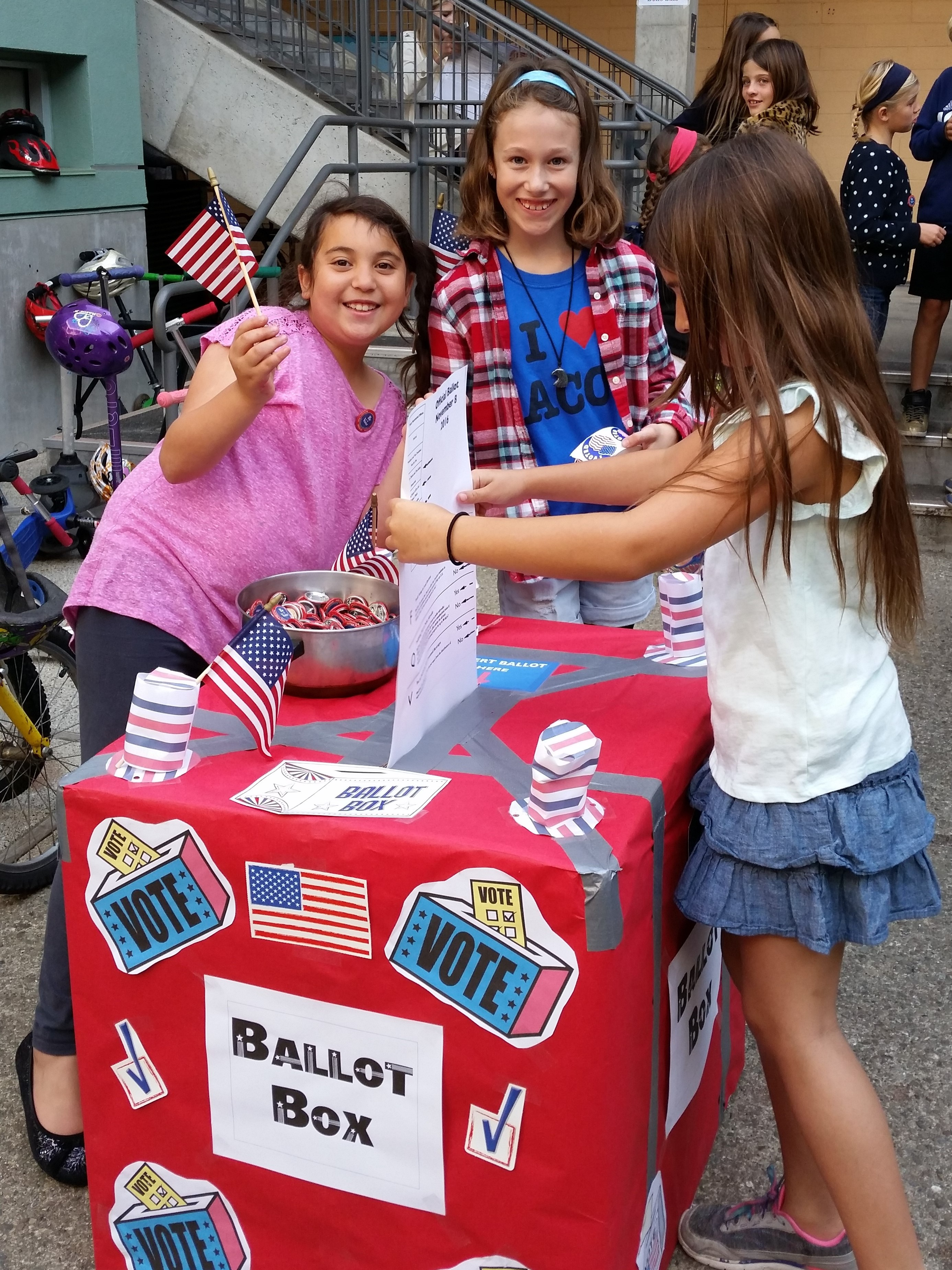 Girls smiling as they use a student ballot box at a school election day event