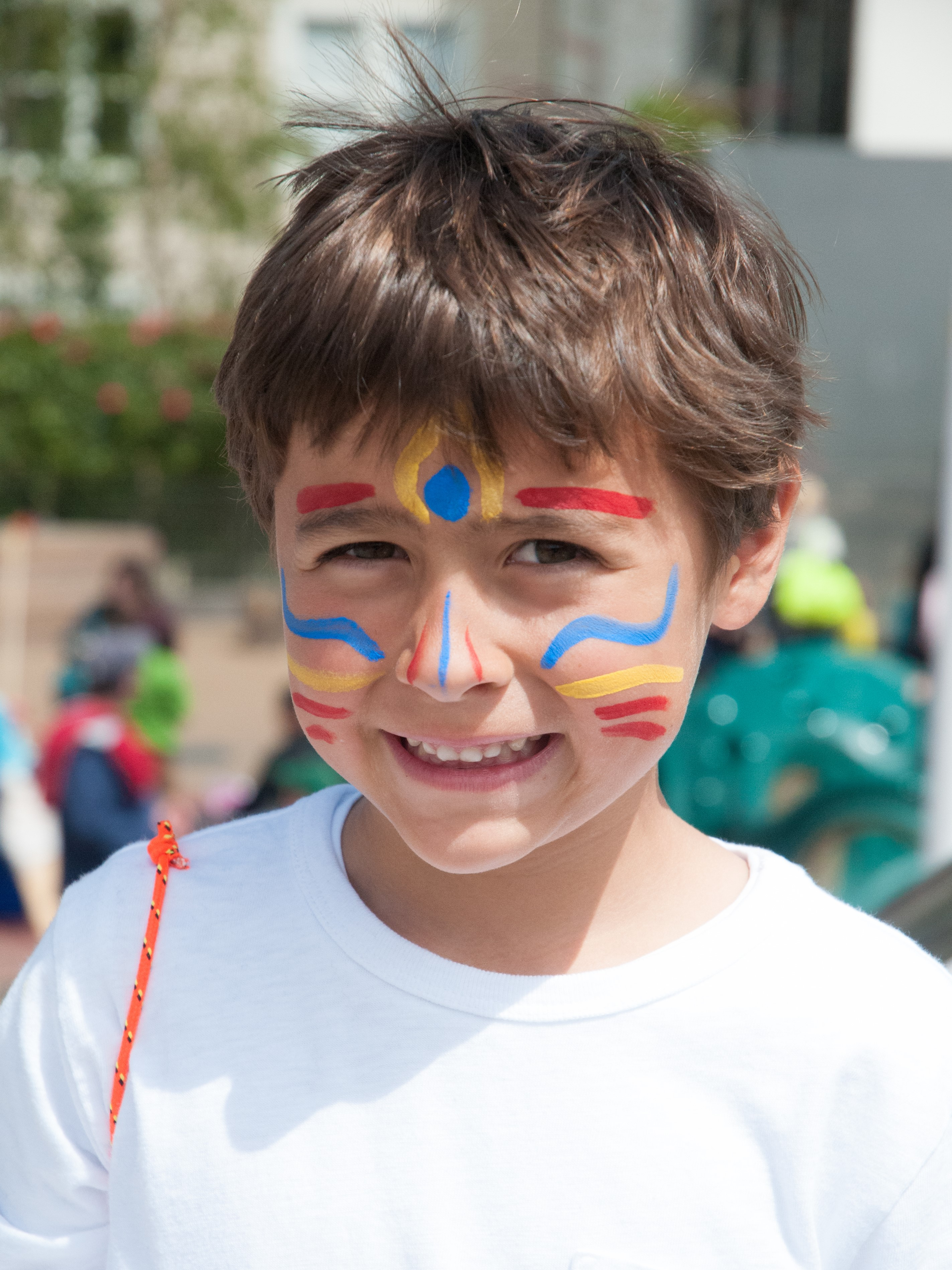 Child with face paint smiles at an outdoor school festival