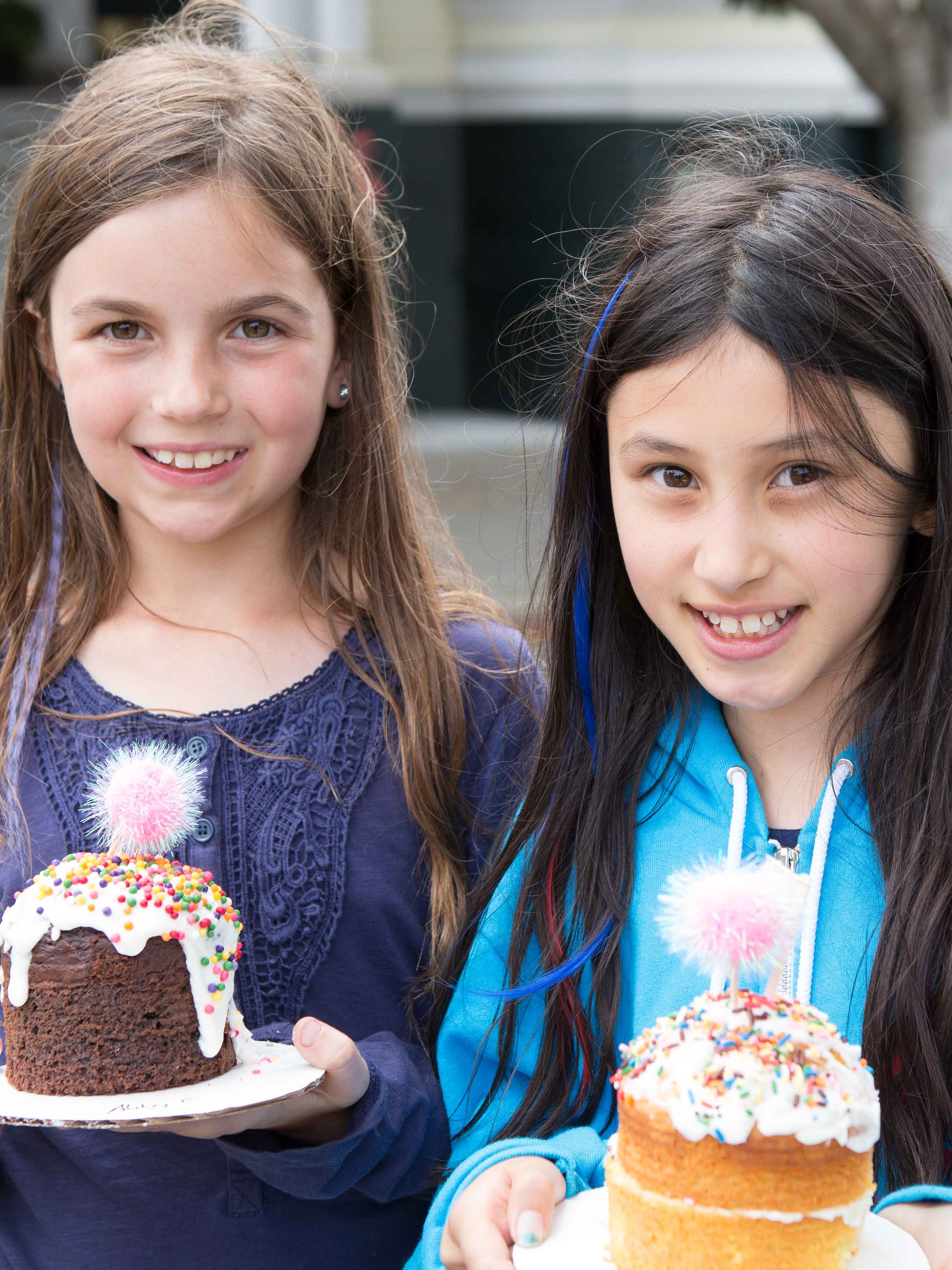 Two girls holding decorated cupcakes at an outdoor school festival