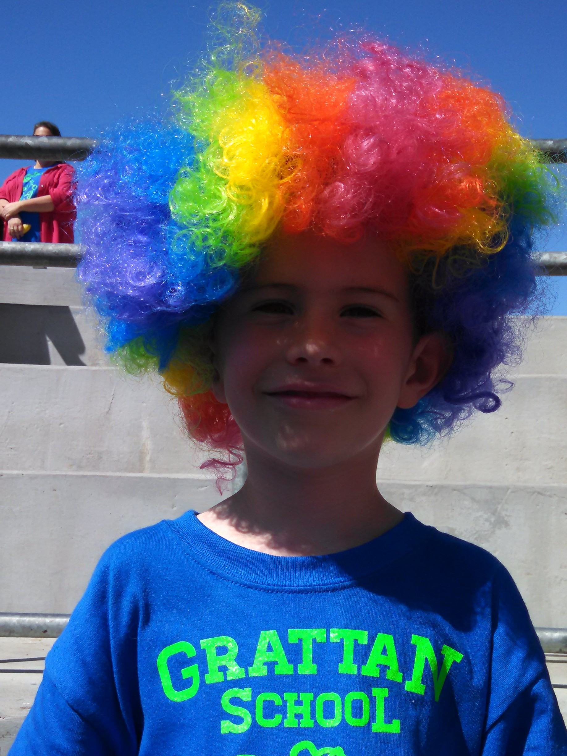 Child wearing rainbow wig at an outdoor school fitness event