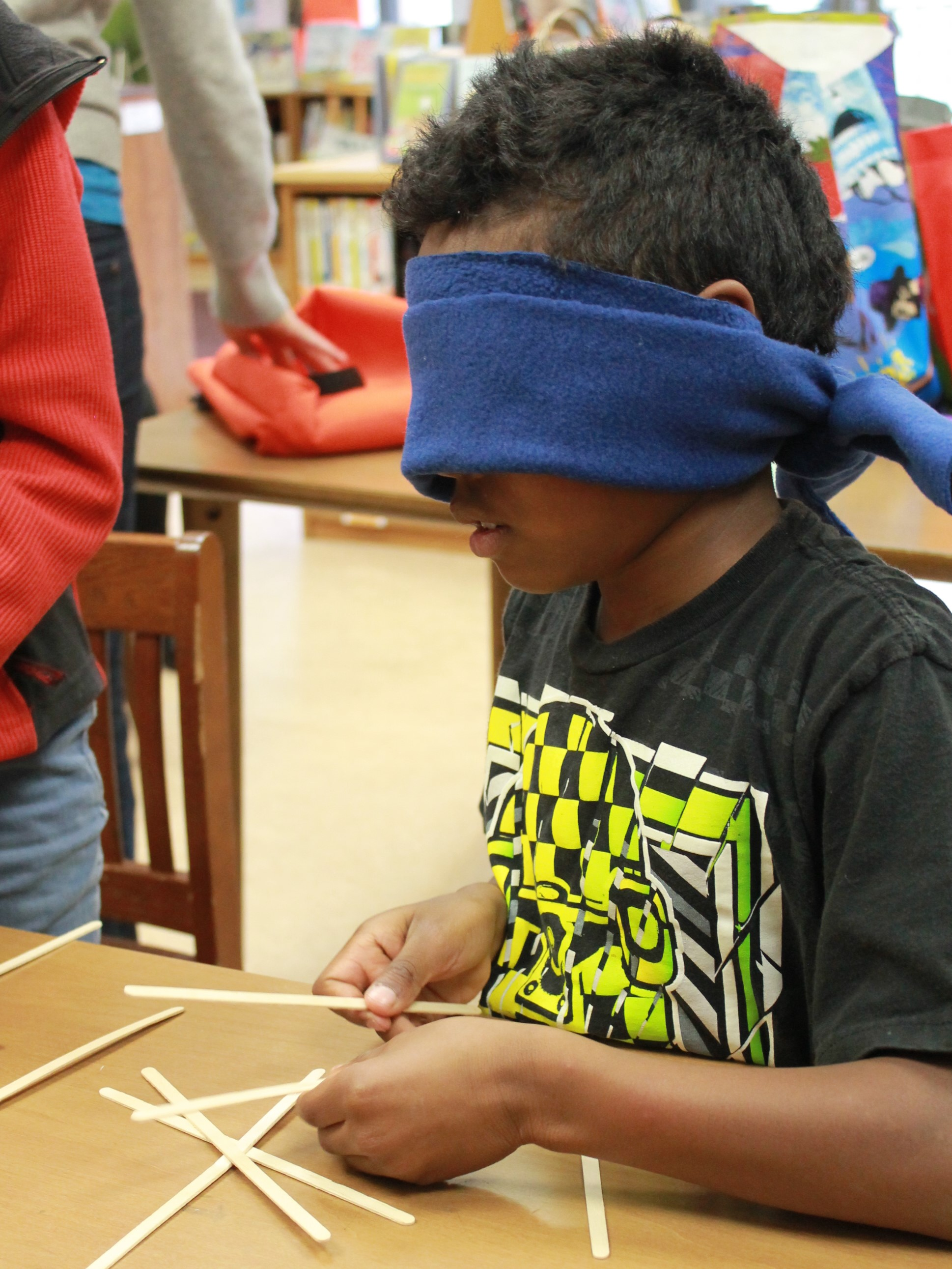 Boy with a blindfold tries to build a structure at a school inclusion awareness event
