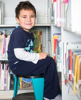 Student sitting on stool in library