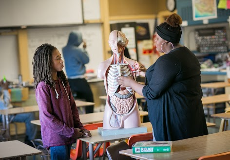 Teacher and student working with model of human body