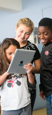 Three students looking at an iPad together
