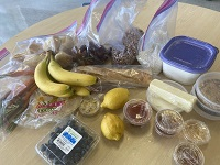 Bananas, berries, condiments, and packaged food as part of a take-home meal kit for Marshall High School's Career Pathways program