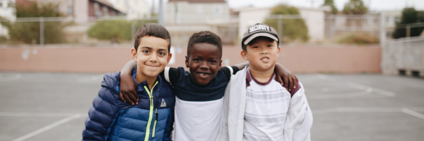Three boys smile on the schoolyard with their arms around each other