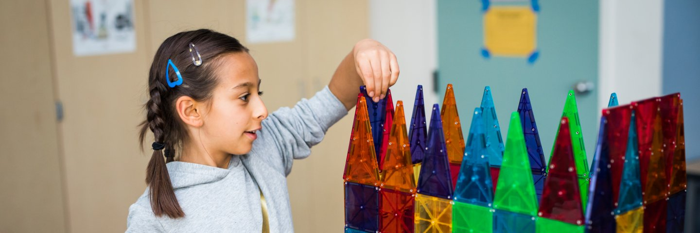 Elementary school student building with magnetic tiles