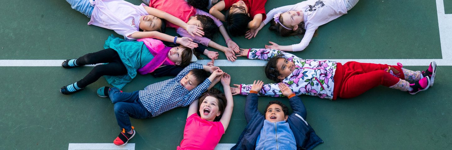 Elementary students lie in a circle with their arms stretched towards each other