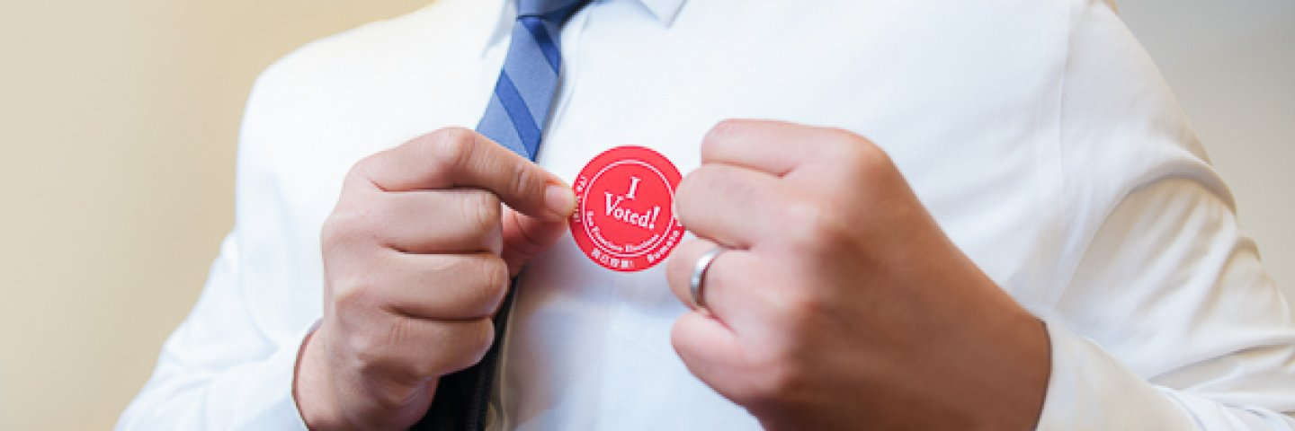 "Person putting on an ""I Voted"" sticker"