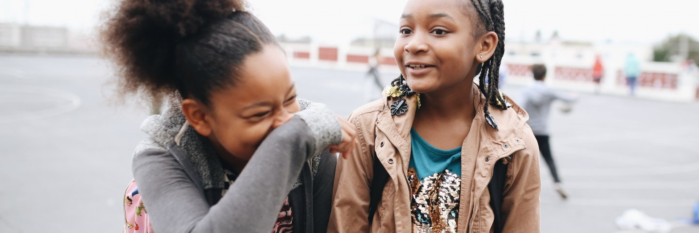Two girls laughing and smiling on the schoolyard