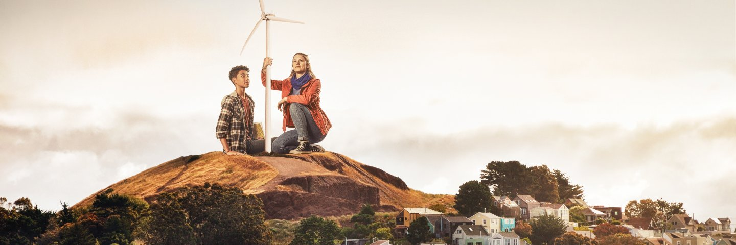 Two students by a wind turbine overlooking San Francisco