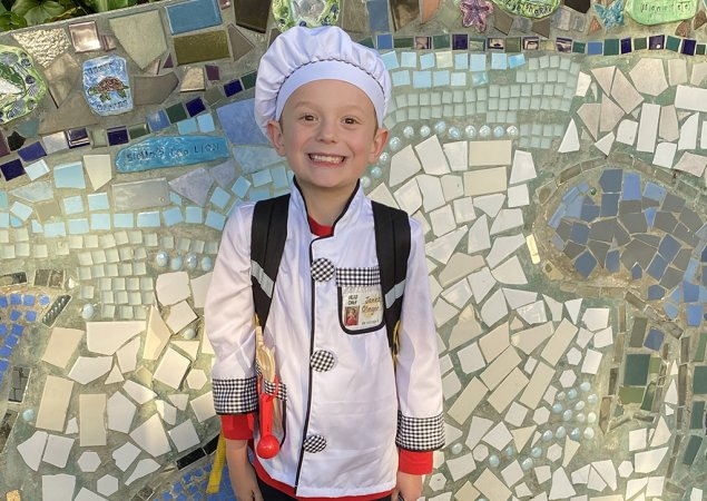 James, a third grader, wears a chef's hat and coat
