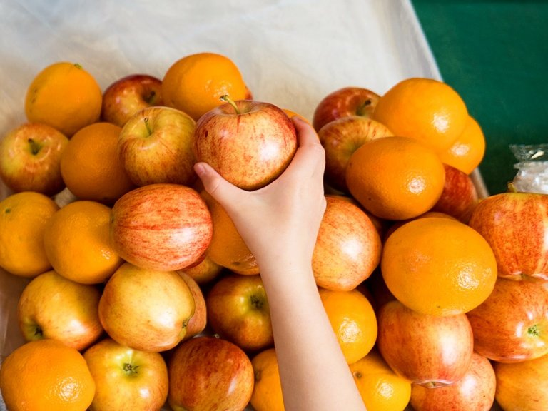 Hand reaching for apples and oranges