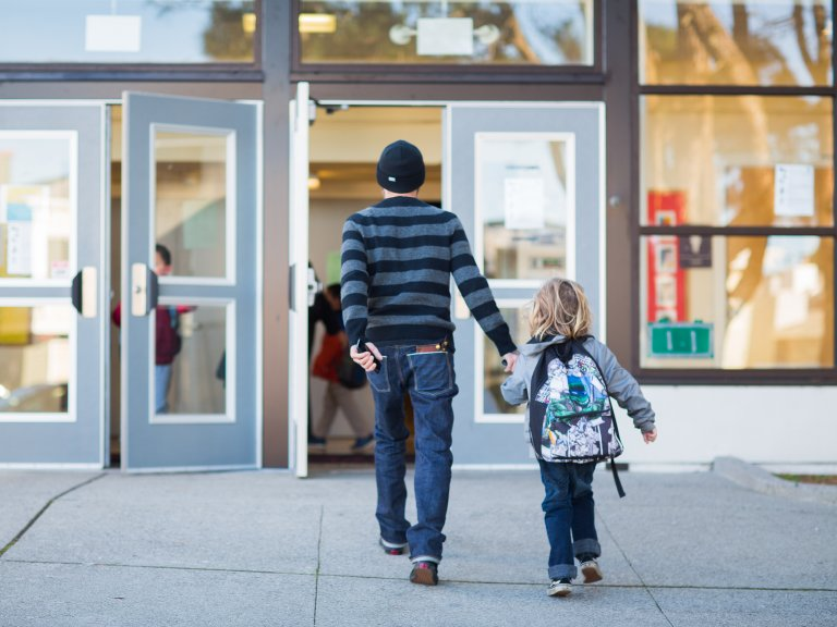 A parent and child walk into a school building together.