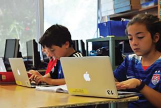 Elementary school students working on laptops