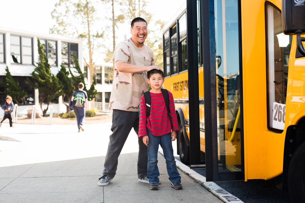Parent/guardian with elementary school student in front of yellow school bus