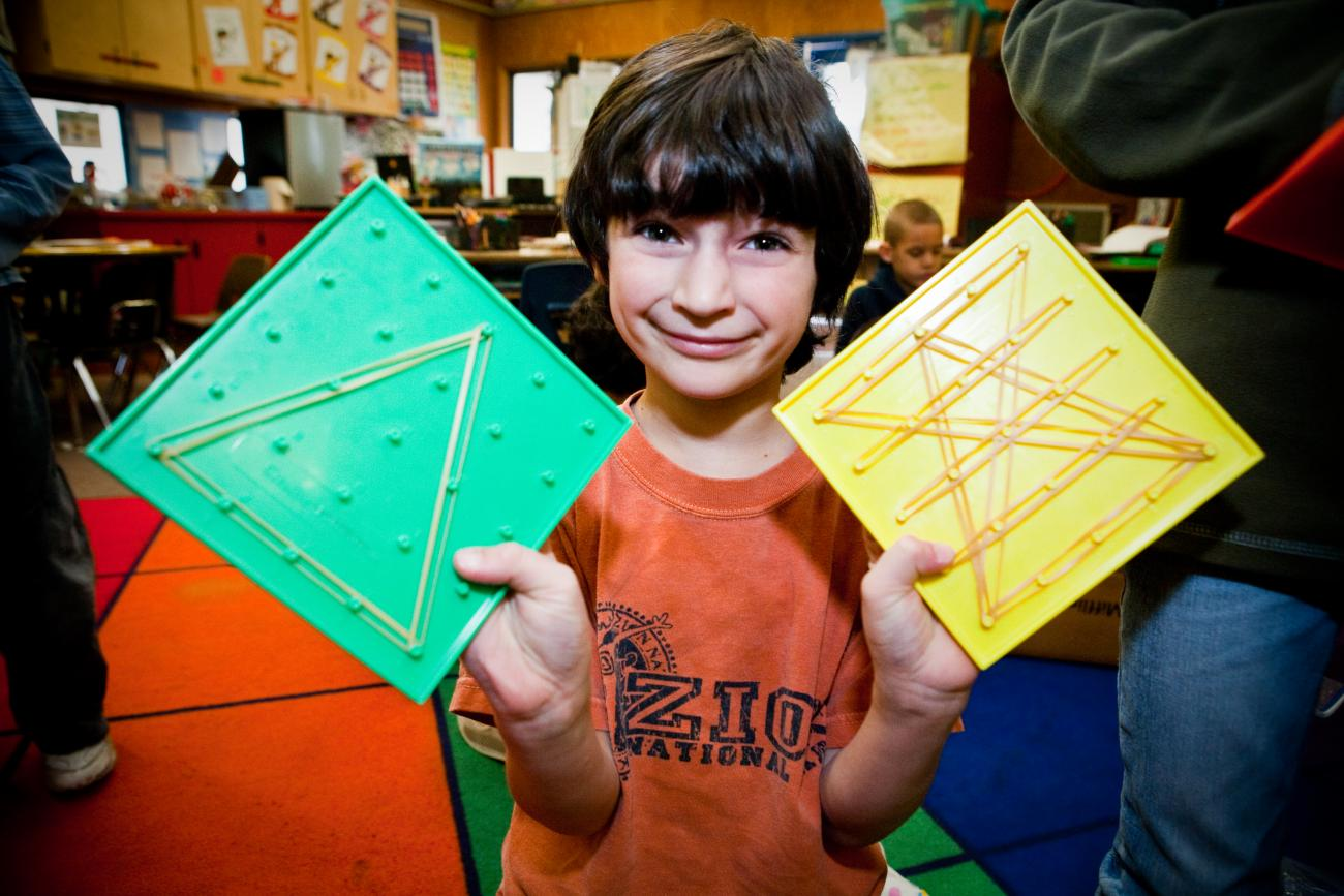 Elementary school student with shapes made with rubber bands