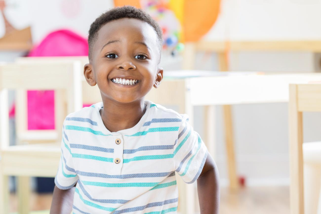 Preschool boy sitting on floor in his classroom and smiling at camera