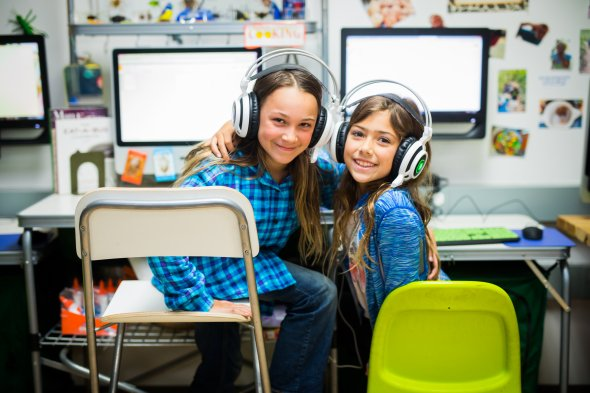 Two girls with headphones in front of computers
