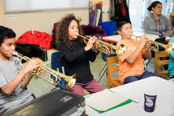Elementary school students playing trumpets