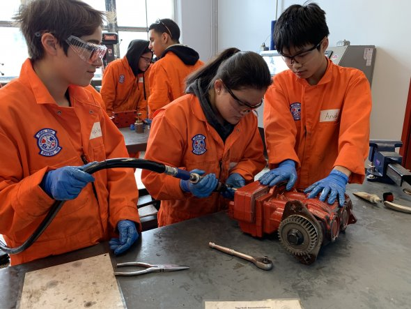 Three students work on a car engine together.