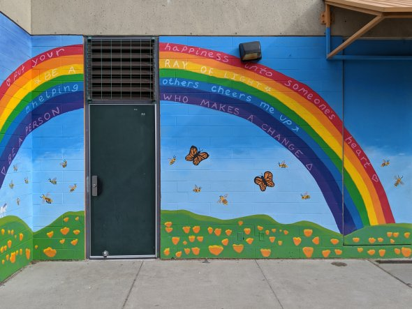 Colorful mural on exterior school wall, including painted rainbow with inspirational sayings