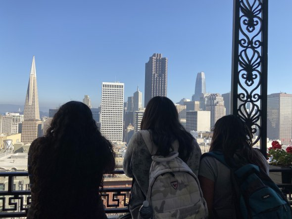 Three students look out from the Fairmont Hotel's and view the cityscape of San Francisco.