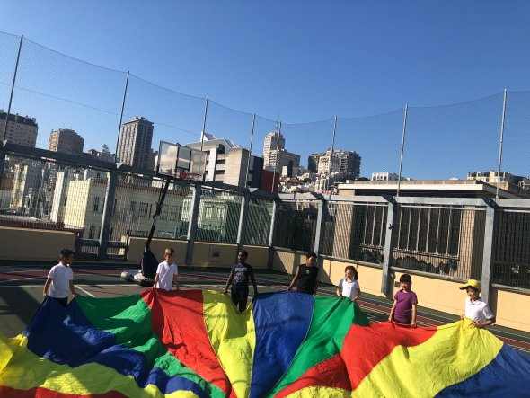 Students play with colorful parachute on schoolyard