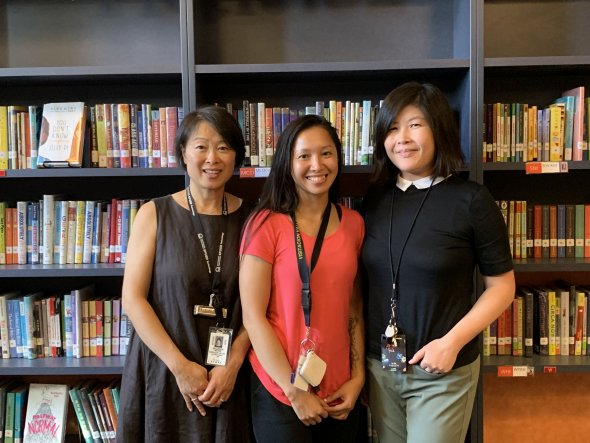 Three women standing behind a bookshelf. From left to right: Maureen Wong, Linda Tran, and Loi Murillo.