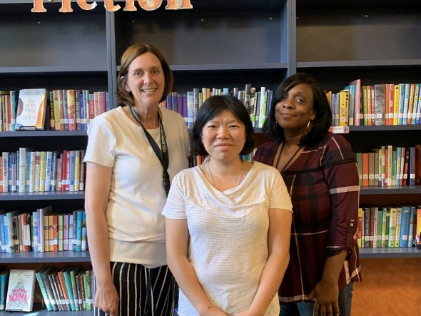Three women standing behind a bookshelf. From left to right: Joy Richardson, Mary Li, and Monique Williams
