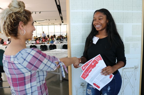 Student shakes hands with an industry partner at a mock interview event.