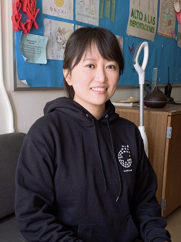 Asian woman with shoulder length hair and in a black sweatshirt with a Wellness logo.