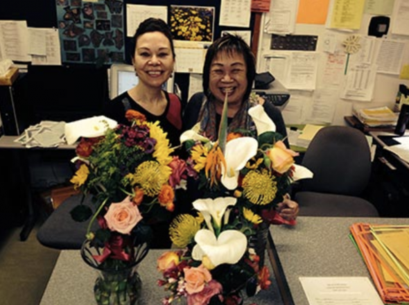 Two female administrative employees pose with flowers