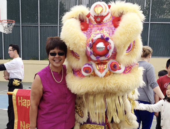 Woman poses with costumed Chinese lion dancer