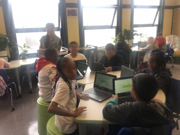 Students working in groups at flexible seating desks, with laptops in front of them, and a teacher in the background
