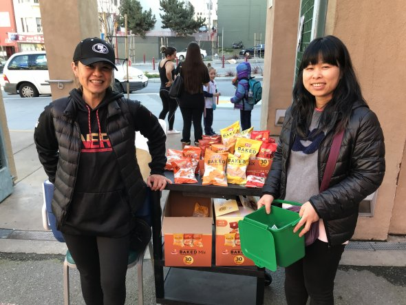 Two smiling Asian women selling snacks