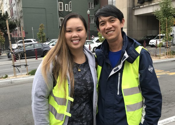 smiling asian woman and man doing drop off duty with yellow vests