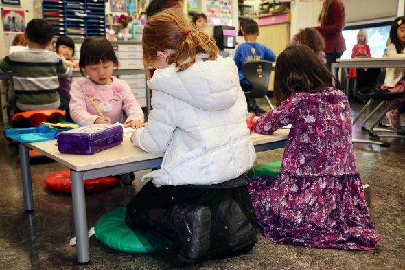 FSK Elementary students sitting on floor cushions at a low table working.