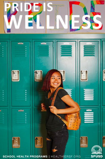 Student smiling in front of lockers with pride sign above them.