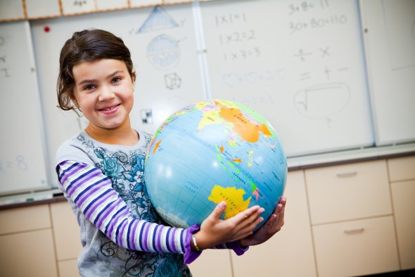 Girl holding globe in classroom