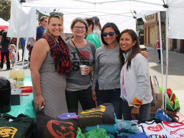 Parent volunteers manage a school spirit wear booth at an outdoor neighborhood festival