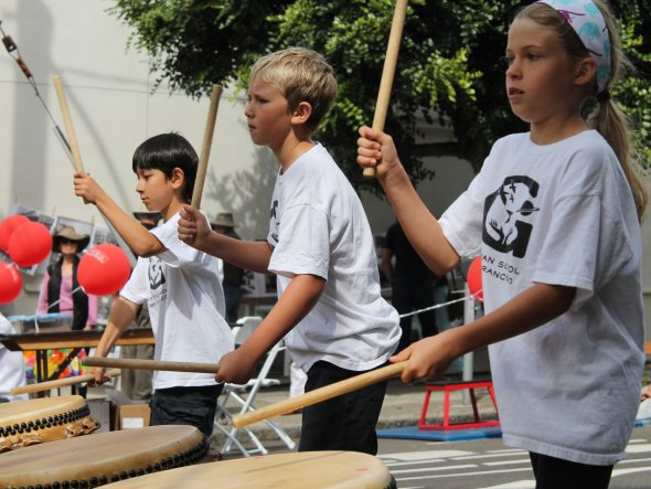 Children perform in a taiko drumming group at an outdoor neighborhood festival