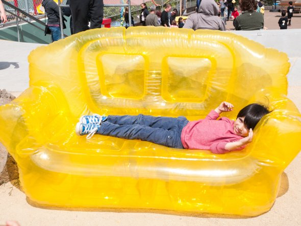 Boy lying in an inflatable yellow couch at an outdoor school festival