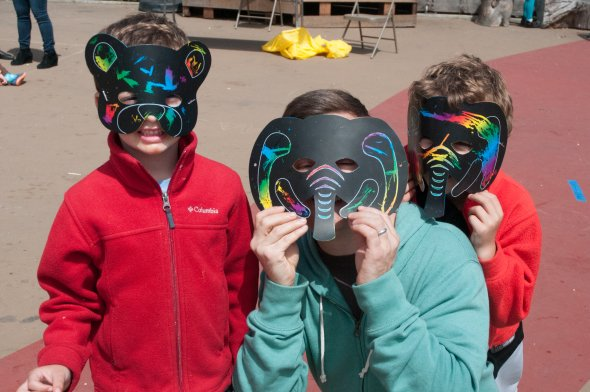 Two children and a parent wearing rainbow animal masks at a school festival